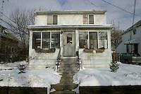 Detroit: paesaggio urbano d'inverno. Una vecchia casa. Intorno prato innevato e altre case.