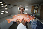 A year after Hurricane Matthew ravaged parts of Haiti, Imose Jean-Baptiste displays a fish in the refrigeration room of a local fishing cooperative in the northwestern Haitian village of Plateforme. The village was ravaged in the storm, and Lutheran World Relief, a member of the ACT Alliance, has helped the community rebuild its economy with fishing materials, this a solar-powered refrigerator room for storing their catch, and other assistance.