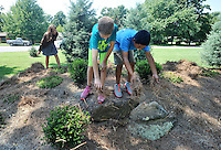 "NWA Democrat-Gazette/MICHAEL WOODS • @NWAMICHAELW<br /> Woodland Junior High 7th graders Gracie Benham, (from left) Gabe Lee and Alex Aldaco help spread mulch around the plants at the ""Garden of Infinite Spirit"" Tuesday September 1, 2015 at Woodland Junior High School in Fayetteville.  The garden, designed by  landscape artist David Slawson, is part of a new outdoor classroom area built in memory of two Woodland teachers, Becky Knight and Jane Coomes, who recently passed away."