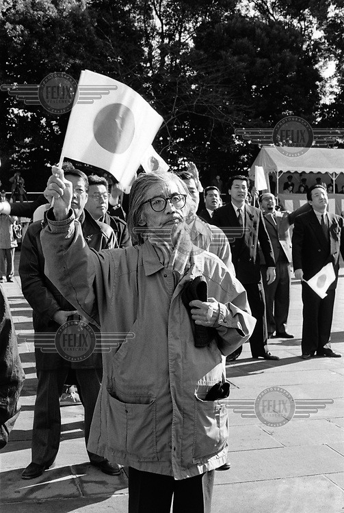 Man cheering Emperor Akihito with the Japanese flag. On the 23 December - the emperor's birthday and a national holiday, he traditionally makes a speech to his subjects and the nation in the courtyard of the Imperial Palace.