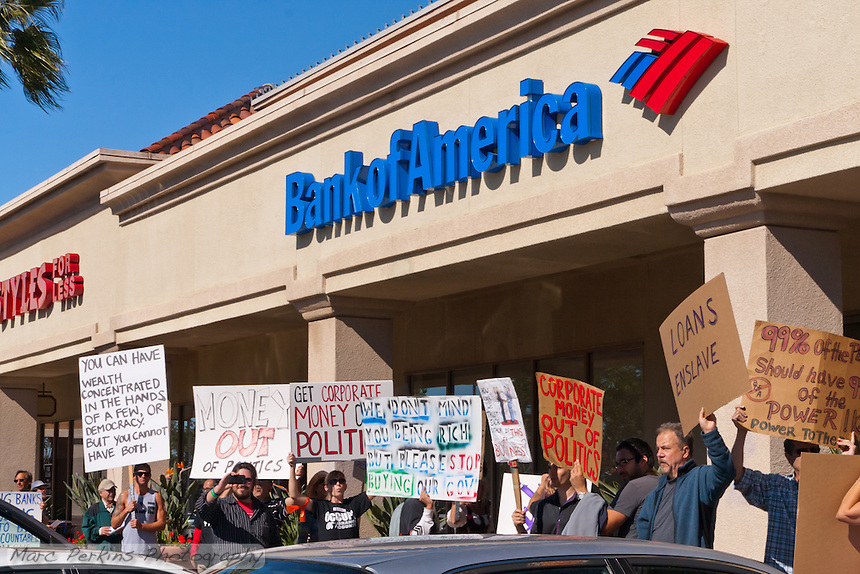 Protesters hold signs in front of a Bank of America in Irvine, CA during the Occupy Orange County, Irvine march on Saturday November 5.