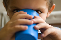 Young boy drinks milk from blue cup