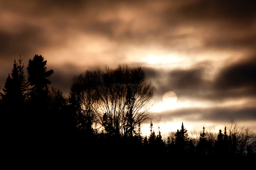 Sun sets in mid winter as seen through heavy cloud cover.