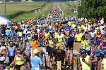 RAGBRAI riders climb on an antique tractor to take photos of the crowd descending on Kesley.