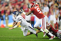 Jan. 1, 2011; Glendale, AZ, USA; Connecticut Huskies quarterback (10) Zach Frazer is sacked in the fourth quarter by the Oklahoma Sooners in the 2011 Fiesta Bowl at University of Phoenix Stadium. The Sooners defeated the Huskies 48-20. Mandatory Credit: Mark J. Rebilas-