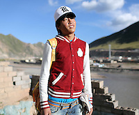 A Tibetan teenager in a relocation village in the Amdo region of the Tibetan Plateau. Up to 100,000 nomads have been removed from the highland grasslands of the Tibetan Plateau. Climate change, mining and government policy are causing the rapid disappearance of this unique culture.