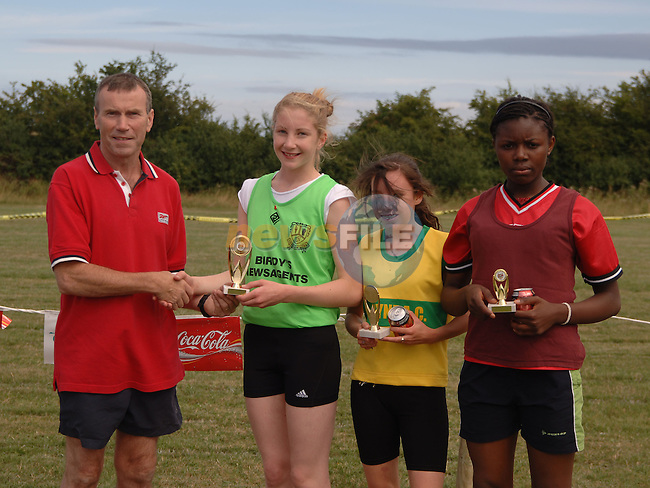August 13, 2006 - Boyne AC Sports Day held at Drogheda, County Louth. Austin Tiernan (Sponsor, Drogheda Concentrates presents first prize to Ann Linden (Carrick Aces), 2nd Aoife Sewell (Boyne AC), and third Royale Chigozie (St Gerards AC)..Photo: BARRY CRONIN/Newsfile..(Photo credit should read BARRY CRONIN/NEWSFILE).