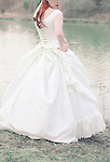 Faceless shot of a young woman and the back of her fancy corset gown, standing in front of a beautiful lake