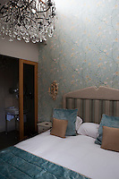 A traditional bedroom with blue floral pattern wallpaper and a double bed with an upholstered headboard. A sliding door leads to an en suite bathroom