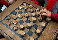 Photo story of Philmont Scout Ranch in Cimarron, New Mexico, taken during a Boy Scout Troop backpack trip in the summer of 2013. Photo is part of a comprehensive picture package which shows in-depth photography of a BSA Ventures crew on a trek. In this photo, a BSA Venture crew passes some time playing on an old chessboard as they waited to tour Hunting Lodge. The lodge is North of Clark's Fork, South of Cimaroncito, and East of Cypher's Mine.<br /> <br /> The  Photo by travel photograph: PatrickschneiderPhoto.com
