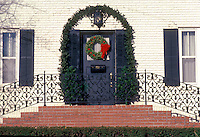 Large brick home with unique wrought iron stair railing decorated with evergreen boughs, bows and ribbons, Midwest USA