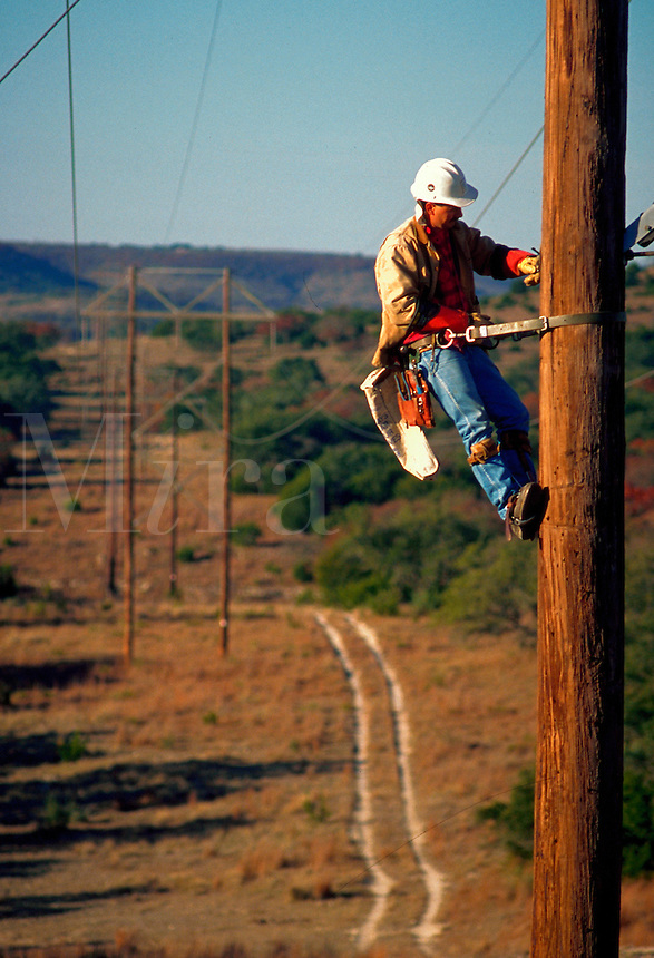A utility worker on a pole.