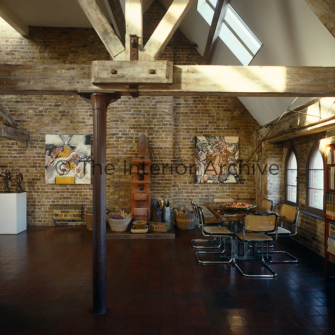 A dining area in one corner of this warehouse apartment which has a polished tiled floor and brick walls and an old-fashioned stove