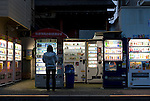 A customer buys cigarettes from vending machines in Tokyo, Japan on 26 April 2010. Photographer: Robert Gilhooly