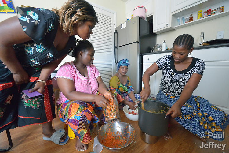 Vumila Masoka (left) looks on as Christina Batachoka, Mwavita Salumu, and Eca Fitina prepare a meal on the kitchen floor of an apartment in Durham, North Carolina. The three women, all refugees from the Democratic Republic of the Congo, were resettled in Durham by Church World Service, which resettles refugees in North Carolina and throughout the United States.<br /> <br /> <br /> Photo by Paul Jeffrey for Church World Service.