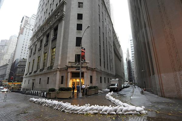 """AGX100. BROOKLYN (ESTADOS UNIDOS), 29/10/2012.- Sacos de arena protegen la entrada del edificio de la Bolsa de Nueva York, Estados Unidos, hoy, lunes 29 de octubre de 2012. El huracán """"Sandy"""", que se encuentra a unos 615 kilómetros al sudeste de la ciudad de Nueva York, sigue ganando fuerza y se espera que traiga una marejada ciclónica junto con vientos de fuerza huracanada, informó hoy el Gobierno. EFE/Andrew Gombert.."""