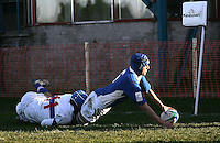 Italy number 6 Lorenzo Puliti scores his team's sixth try despite the efforts of Chen-Wen Li of Chinese Taipei in the pool match of Division B of the Under 19 Rugby World Cup played at Gibson Park Belfast.