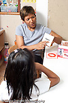 Education Preschool 3-5 year olds female teacher working with child on letter sounds and associations using picture cards vertical