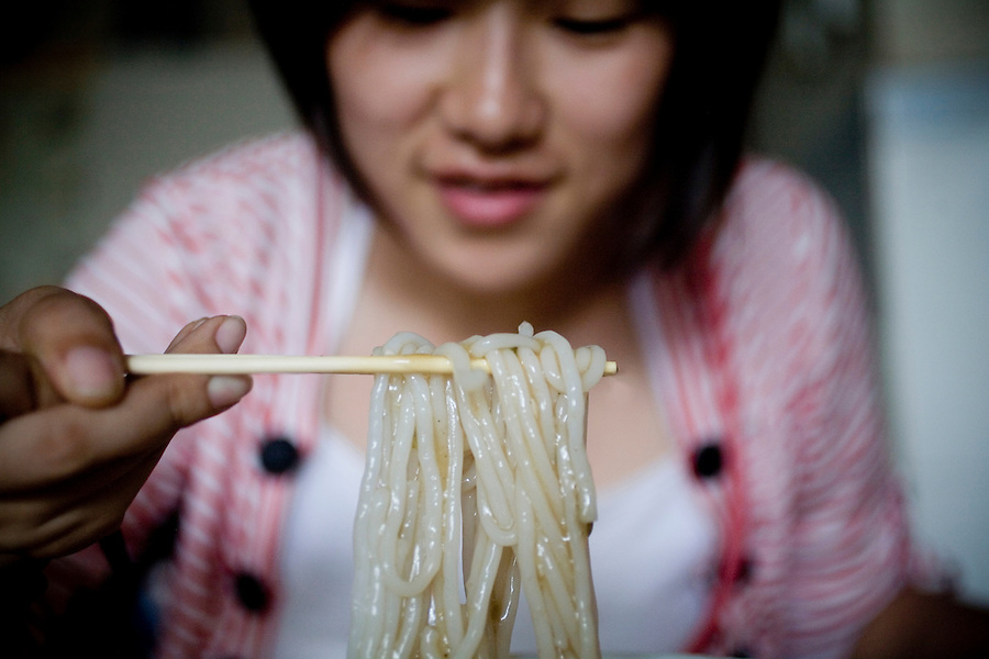 A woman uses chopsticks to eat a bowl of rice noodles at Bao Luo Fen, popular local restaurant in Sanya, China.