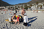 CAMPS BAY, SOUTH AFRICA - MARCH 20: Mostly white beach goers Camps Bay beach on March 20, 2012 in Cape Town, South Africa. Africans sell art or beg for money on the beach. (Photo by Per-Anders Pettersson)