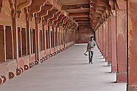 Indian worker framed by columns, Fatehpur Sikri, in the state of Uttar Pradesh, India.