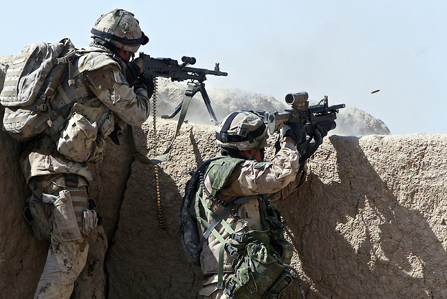 Cpl. Kevin Foster and Warrant Officer Mike Saunders exchange fire with Taliban fighters in the village of Pashmul in Zhari district, Kandahar province, Afghanistan. The two soldiers are with a Canadian team that is mentoring Afghan troops in Zhari, where they fight daily skirmishes with insurgents. The district is where the hardline Taliban movement originated in the early 1990s. Sept. 29, 2008. DREW BROWN/STARS AND STRIPES