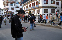 A modern Bhutanese boy wearin western clothes surfs through his mobile at Thimpu market. Arindam Mukherjee..