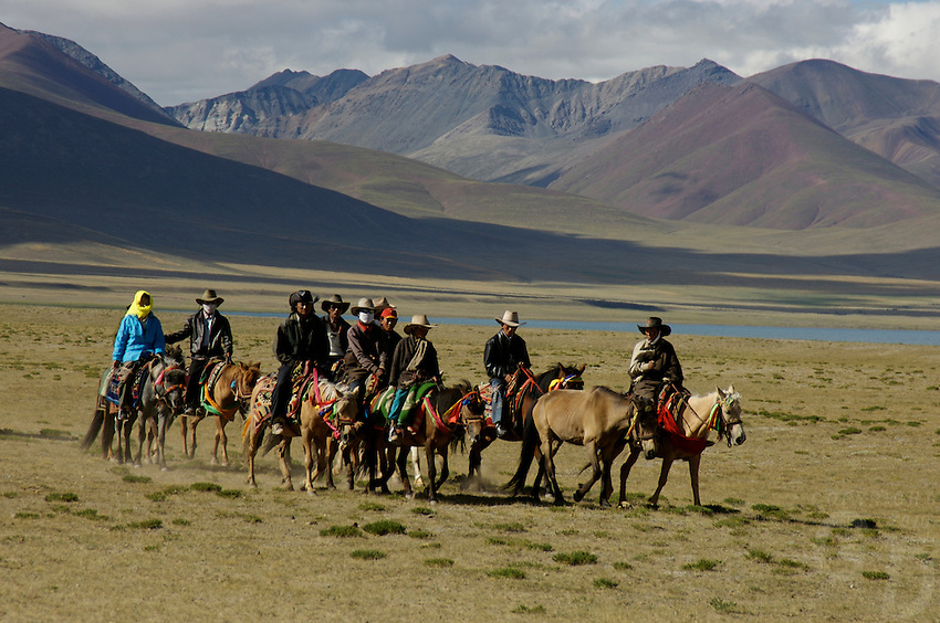 """Early morning Nomads on horseback at the edge of Namtso Lake.Namtso Lake :Namtso, another holy lake in Tibet, is located near Damxung. 4718 meters (15475 feet) above sea level and covering 1900 square kilometers (735 square miles), the lake is the highest saltwater lake in the world and the second largest saltwater lake in China. The snow capped Mt. Nyainqentanglha, considered as the son of Namtso and leader of sacred mountains, soars up to sky beside her. Singing streams converge into the clean sapphire blue lake, which looks like a huge mirror framed and dotted with flowers..The Namtso Lake is held as """"the heavenly lake"""" or """"the holy lake"""" in northern Tibet. .Respected as one of the three holiest lakes in Tibet, the Namtso Lake is the seat of Paramasukha Chakrasamvara for Buddhist pilgrims. In the fifth and sixth month of the Tibetan calendar each year, many Buddhists come to the lake pay homage and pray. Deep tracks are worn into the lakeshore due to this activity. In history, monasteries stood like trees in a forest around the site, attracting large numbers of pilgrims as eminent monks in Buddhist temples extended Buddhist teachings...Buddhists believe Buddhas, Bodhisattvas and Vajras will assemble to hold religious meeting at Namtso in the year of sheep on Tibetan calendar. It is said that walking around the lake at the right moment is 100,000 times more efficacious than that in normal years. That's why thousands of pilgrims from every corner of the world come to pray at the site, with the activity reaching a climax on Tibetan April 15...Walking around the lake takes a week. Ritual walkers love to burn aromatic plants to raise smoke on Auspicious Island [explain this a little] and throw a piece of hada scarf into the lake as a token of fulfilled wishes. If the scarf sinks, it implies ones wish is accepted by the Buddha; if the scarf flows on the water or only half sinks, it means one has failed to be honest and something unhappy may lie ahead...On the four side"""