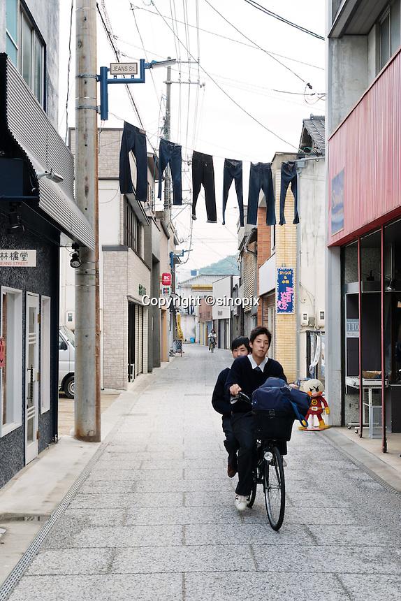MAY 15, 2014 - KOJIMA, KURASHIKI, JAPAN: students on bicycle pass Jeans Street.  (Photograph / Ko Sasaki)