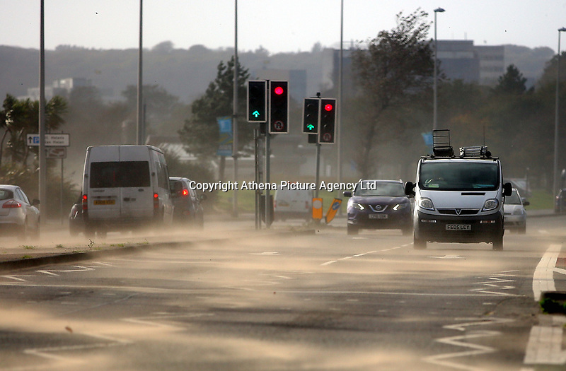 """Pictured: Cars traveling on Oystermouth Road get blasted by sand blown from the beach in Swansea, UK. Monday 16 October 2017<br /> Re: Remnants of Hurricane Ophelia are expected to bring strong gusts of wind to Wales when it hits Britain's shores.<br /> The hurricane, making its way from the Azores in the Atlantic Ocean, will have weakened to a storm when it arrives.<br /> A Met Office amber """"be prepared"""" warning has been issued in some areas bringing """"potential danger to life""""."""