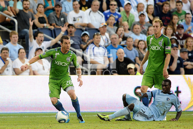 Zach Scott (20) defender Seattle Sounders moves away from C.J Sapong (17) forward Sporting KC on the ground... Sporting Kansas City were defeated 1-2 by Seattle Sounders at LIVESTRONG Sporting Park, Kansas City, Kansas.