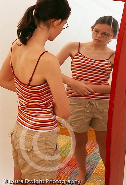 Teenage girl 12 years old looking at self in destorted mirror vertical