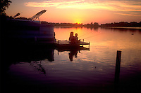 Aunt and niece fishing off dock at sunset age 50 and 5.  Campbellsport  Wisconsin USA