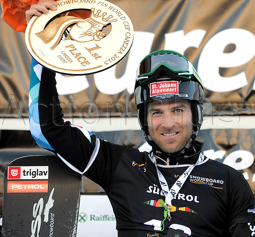 13.12.2013  CAREZZA, ITALY. Mens  SNOWBOARD FIS World cup Parallel. Anton Unterkofler (AUT) on the podium with his trophy