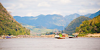 Panoramic Photo of the Slow Boat from Thailand to Vientiane, Laos on the Mekong River. This panoramic photo shows the slow boat from Huay Xai in North Thailand to Vientiane in Laos, which takes two days and is a very popular way for tourists to cross the border from Thailand into Laos. The slow boat travels down the Mekong River, stopping off at Pak Beng for one night on the way.