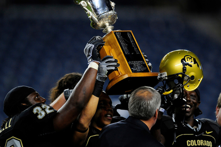 31 Aug 2008: University of Colorado Buffaloes football players Maurice Cantrell (32), Ryan Walters (under trophy) and Patrick Williams (at right) raise a trophy into the air. The trophy is presented annually to the winner of the CU-CSU in-state rivalry.  The Colorado Buffaloes defeated the Colorado State Rams 38-17 at Invesco Field at Mile High in Denver, Colorado.