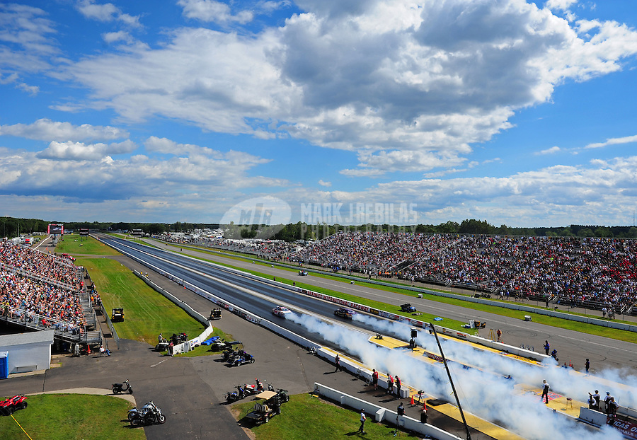 Aug. 21, 2011; Brainerd, MN, USA: NHRA pro stock driver Greg Anderson (near lane) does his burnout alongside Vincent Nobile during the Lucas Oil Nationals at Brainerd International Raceway. Mandatory Credit: Mark J. Rebilas-