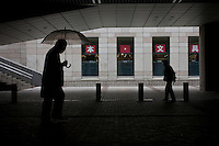 An office worker carrying an umbrella a tourist walk through the underground passages of the Tokyo Metropolitan Government Building. Shinjuku, Tokyo, Japan. Friday November 11th 2011