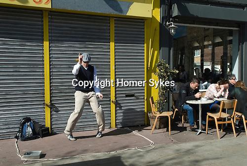 Hackney,Chatsworth Road,Man doing street dance, people enjoying Sunday morning coffee. London Uk