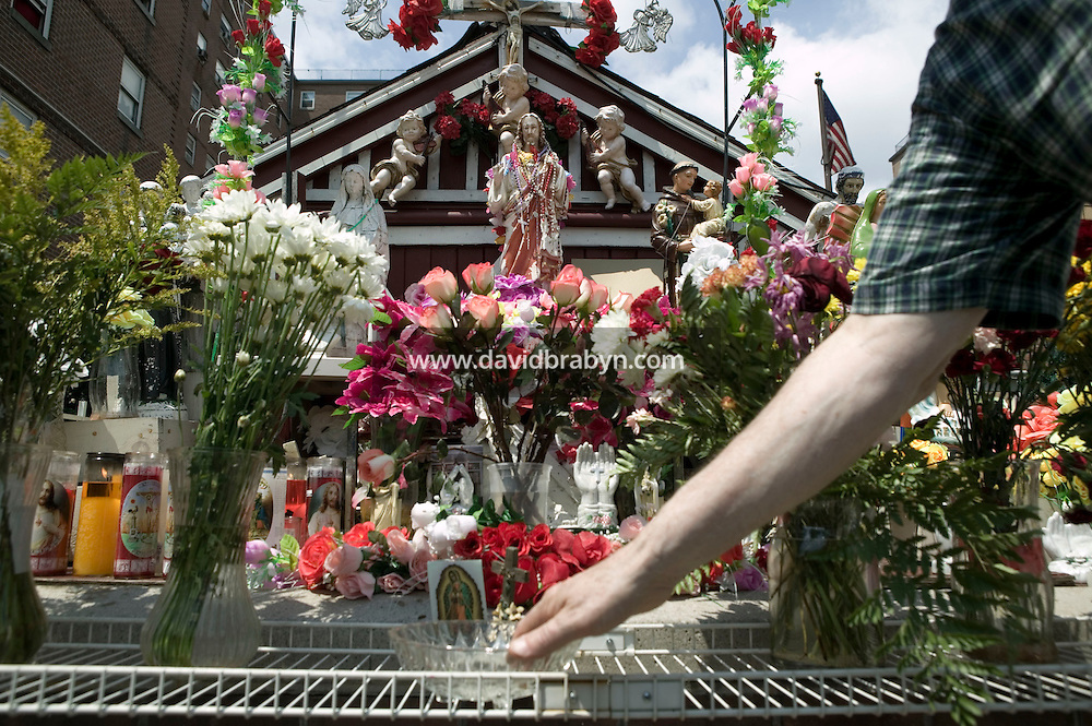 A man dips his hand into a bowl of holy water in front of a statue of Christ that rests in a small shrine on Jackson and Third streets in Hoboken, NJ, USA, to examine the eye that is said to have suddenly opened without human intervention a few days earlier in what locals believe is a sign from God, 31 July 2005. Photo Credit: David Brabyn