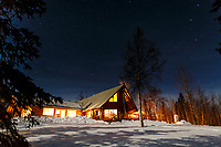 Night time winter photo of main lodge at Winter Lake Lodge with stars. Southcentral, Alaska.