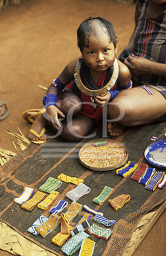 Xingu, Brazil. Kayapo toddler with shaved head and intricate face and body paint with woman making beadwork bracelets A-Ukre village.
