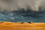 Sahara sand dunes with stormy, cloudy sky and rainbow at Erg Lihoudi, M'hamid, Morocco.
