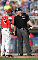 Umpire Dave Albertson explains a call to manager Angel Espada (4) during a game between the Lowell Spinners and Batavia Muckdogs on July 18, 2014 at Dwyer Stadium in Batavia, New York.  Lowell defeated Batavia 11-2.  (Mike Janes/Four Seam Images)