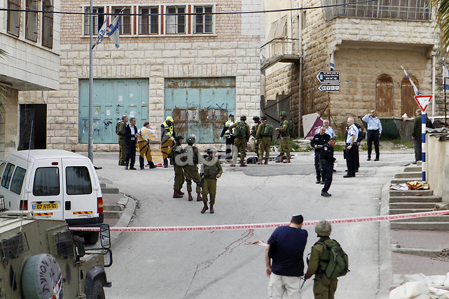 Israeli security forces carry the body of a Palestinian man tried to stab an Israeli soldier before being shot dead, in the Israeli occupied West Bank city of Hebron, on March 24, 2016. Two Palestinians were killed by Israeli forces Thursday morning after allegedly carrying out a stabbing attack and lightly injuring an Israeli soldier in the Tel Rumeida area of Hebron, an Israeli army spokesperson said. Photo by Wisam Hashlamoun
