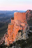 "Queribus Castle or Chateau de Queribus, Cathar Castle, Cucugnan, Corbieres, Aude, France.  Evening view showing the steep cliffs of its hilltop location and Pyrenees in the distance. This castle, built from 13th to 16th centuries, is considered the last Cathar stronghold. It sits on a high peak at 728m. It is one of the ""Five Sons of Carcassonne"" or ""Cinq Fils de Carcassonne"". It is a listed monument historique and has been fully restored, restoration work being completed in 2002. Picture by Manuel Cohen"