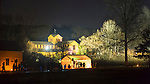 Old Bethpage, New York, USA. Decemer 26, 2014. At night, the historic, sweeping rustic grounds of Old Bethpage Village Restoration are transformed by candlelight and Christmas decorations into a Nineteenth Century holiday experience for Long Island visitors. Family fun included recreations of 1800's music with a trio of singers in an open front tent. Candlelight Evenings are held until December 30th.