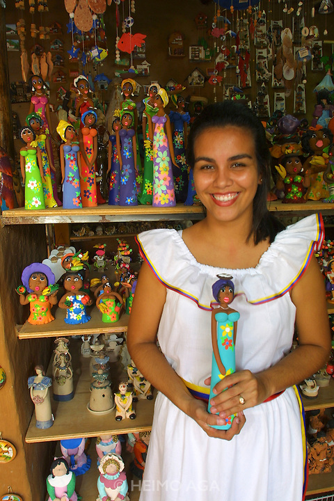 Girl selling souvenir Mulata dolls for tourists.