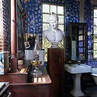 A bust of Mars stands proudly on a plinth between the basin and chest of drawers in the bathroom