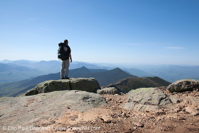 A hiker takes in the view from along the Appalachian Trail, on the summit of Mount Lincoln, in the White Mountains of New Hampshire USA during the spring months.